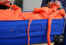 aus dem blauen Rollkoffer drängt eine orangefarbene Wollplastik in den Raum