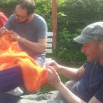 cozy chaos strickattacke im Schrebergarten Bochum. Drei Männer stricken an einem orangefarbenen Kunstobjekt, welches aus einem blauen Rollkoffer wächst.